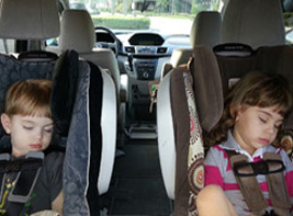 Two kids sleep on car